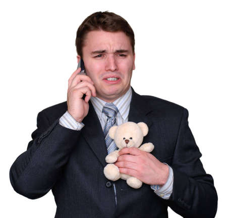 Young businessman clutching a small teddy bear, crying and talking on a cell phone. Isolated on white. Stock Photo