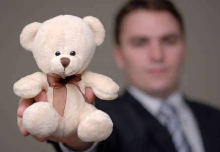 Young businessman holding teddy bear towards the camera. Shallow depth of field. Stock Photo