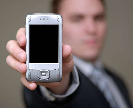 Young businessman holding cell phone towards the camera. Shallow depth of field.