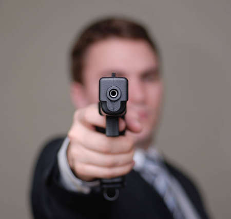 Young businessman pointing a gun towards the camera. Shallow depth of field.