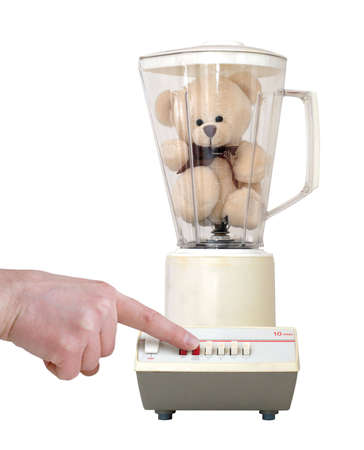 Cute little teddy bear in an old-fashioned blender, with a finger pushing the button. Isolated on a white background.