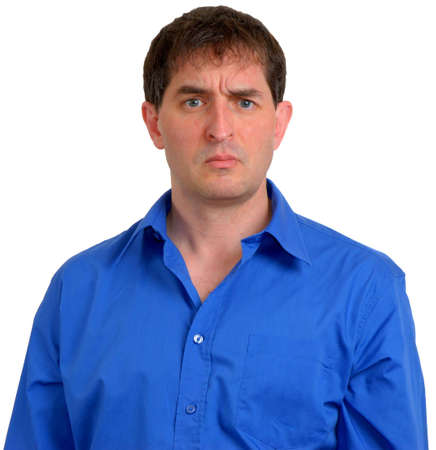 Man in blue dress shirt looking slightly skeptical. Stock Photo