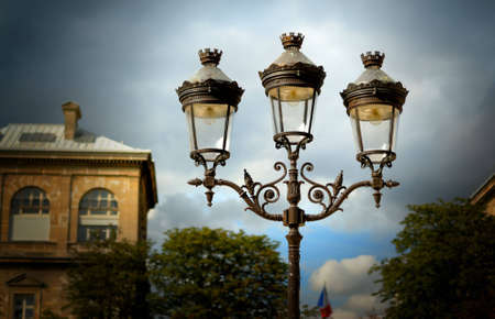 Decorative lamps against a cloudy sky outside of Notre Dame Cathedral in Paris, France, with building in the background. Stock Photo