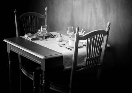 Black and white image of a small and charming restaurant table in Provence, France. This image has a film grain effect added to it.