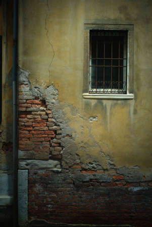 Crumbling wall in Venice, Italy, with exposed brick, a barred window and a pipe. Image has a light pastel on canvas effect added to it.