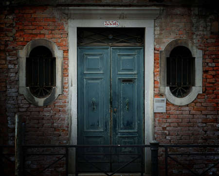 Crumbling weathered entrance to a building in Venice, Italy, with red brick wall, ornate barred windows and blue wooden door. photo