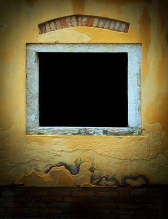 적합: Window in weathered yellow plaster wall with red brick along the bottom in Venice, Italy. Dark window area is suitable for inserting text or image. Image has added film grain effect 스톡 콘텐츠