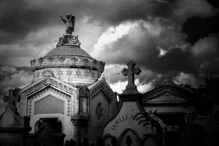 Black and white image of a stone mausoleum and tombstones iin an ancient cemetery in France. Image has photo grain effect added.