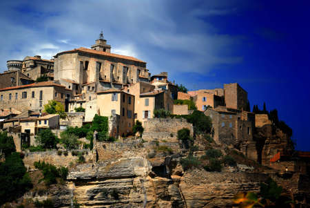gordes: View of ancient medieval hilltop town of Gordes in France, under a dramatic, partly cloudy sky. Stock Photo