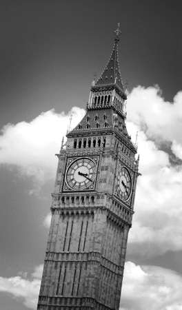 Black and white image of Big Ben clock tower in London, England, against dramatic clouds. Image has an added film grain effect. Stock Photo