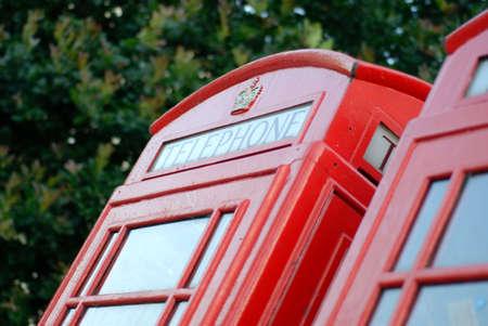 cabina telefonica: Detalle de una cabina de tel�fono rojo en Londres, Inglaterra, con hojas en el fondo Foto de archivo