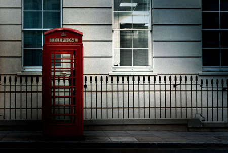 Moody, artistic image of lone red phone booth with lit window behind and to the right. Image has a film grain effect added.