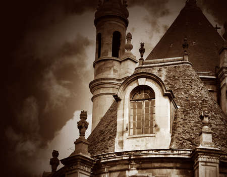 Sepia toned image of an ancient building in Paris, France, against a dramatic cloudy sky. Image has an added film grain effect.