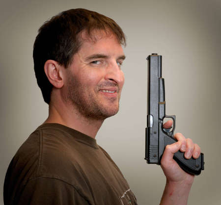 sidelong: Smiling, slightly crazy-looking man looking sidelong at camera, holding gun up in front of him.