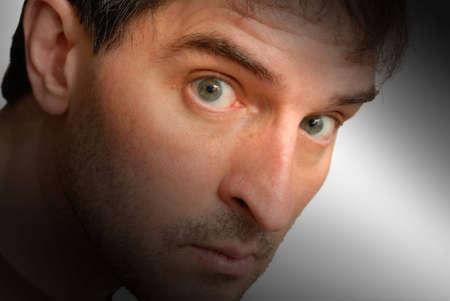 sidelong: Isolated close-up shot of a man looking sidelong at the camera. Stock Photo