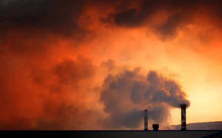 Steam or smoke billowing from chimneys on a cold day at dawn.