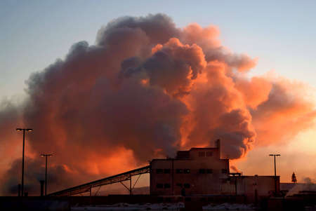 Factory at dawn on a cold day, with steam or smoke billowing from its chimneys. Stock Photo