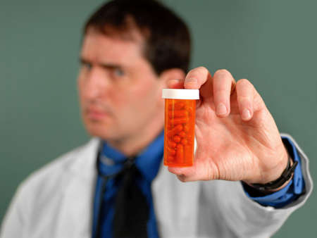 Doctor showing bottle of pills, shallow DOF. Stock Photo