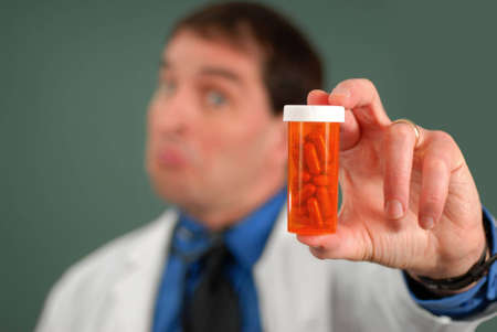 Doctor with questioning look showing bottle of pills, shallow DOF.