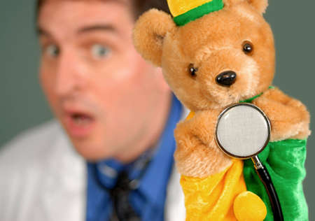 Surprised doctor using a bear puppet to hold a stethoscope.
