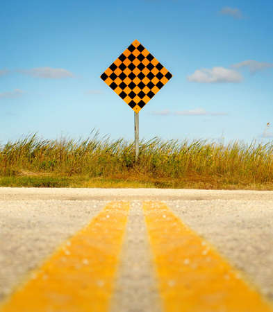 Double yellow lines on paved road leading to dead end sign against a blue sky. Stock Photo