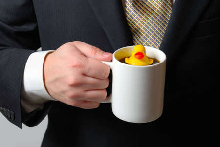 Yellow rubber ducky floating in a coffee cup being held by a man in a business suit.