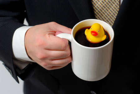 rubber ducky: Yellow rubber ducky floating in a coffee cup being held by a man in a business suit.