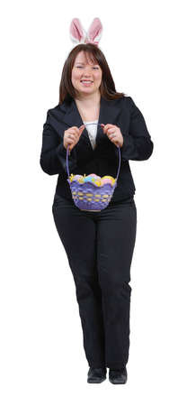 Young woman wearing suit with Easter Bunny ears, holding an Easter basket full of brightly coloured eggs.