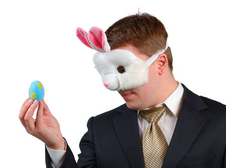 Young man wearing suit with Easter Bunny mask, looking at an Easter egg which he is holding in front of his face.