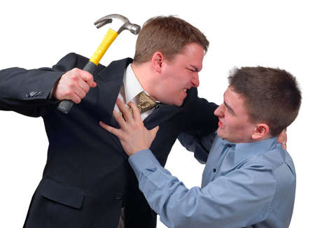 Angry young man in a business suit attacking a frightened young man in a dress shirt with a hammer. Stock Photo