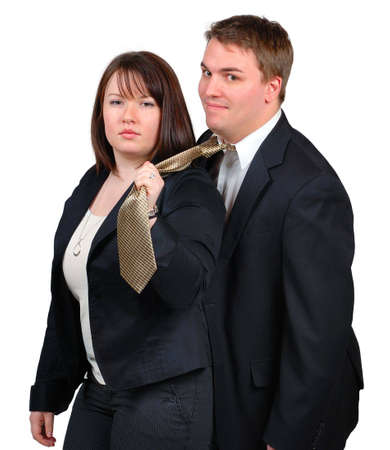 Young couple in business attire. Woman is holding man by the tie, as if by a leash. Man looks happy.