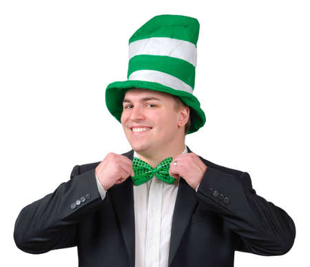 Young man wearing suit with green novelty hat, straightening green bow tie for St. Patrick's Day. Isolated Stock Photo