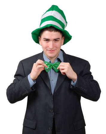 Young man wearing suit with green novelty hat, straightening green bow tie for St. Patricks Day. Isolated