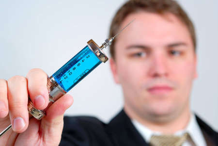 Man wearing business suit and holding an antique, blue liquid filled glass syringe towards the camera, with shallow depth of field.