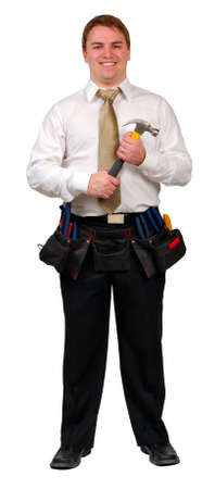 Man in business attire wearing a tool belt, holding a hammer and smiling. Isolated Stockfoto