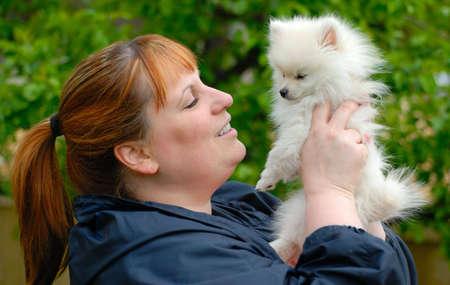 Woman holding an adorable white pomeranian puppy.