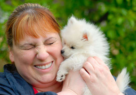 Woman holding an adorable white pomeranian puppy.