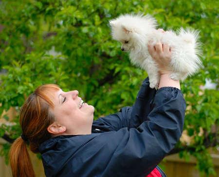 Smiling woman holding an adorable white pomeranian puppy. Stock Photo