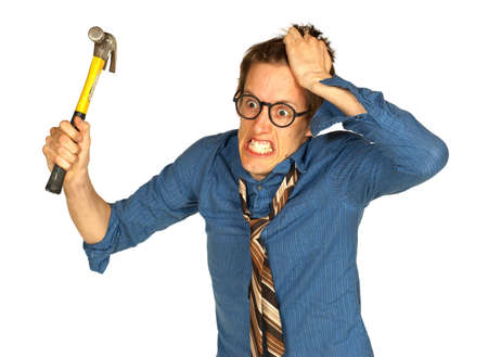 Frustrated, angry man with his hand in his hair, brandishing a hammer, isolated on white background
