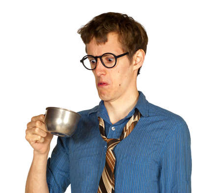 Man with glasses looking into metal cup, with look of distaste, isolated on white background