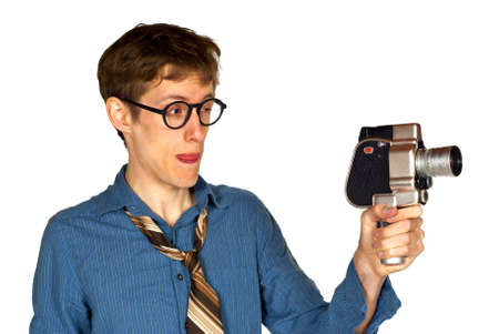 Man with shirt and tie and glasses looking through a hand-held vintage movie camera, isolated on white background  Stock Photo