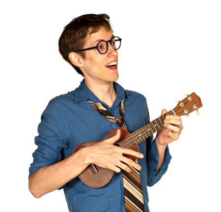 Happy man looking off to the side while playing a ukelele and singing, isolated on white background