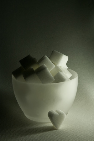 A translucid bowl of white lump sugar, on semi-dark background.