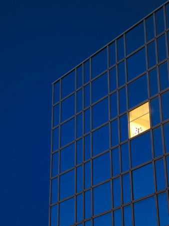 A yellow window in a royal blue office building against a royal blue sky Stock Photo