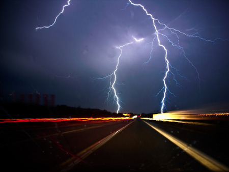 Two forks of bluish-white lightning strike on either side of a dark highway at night, materialized by the streaks of taillights and headlights