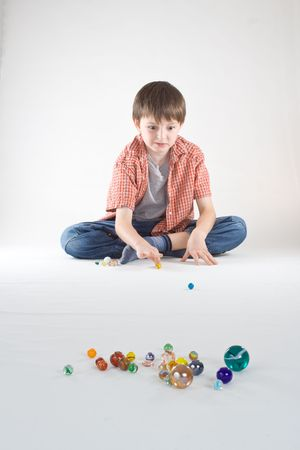 A boy plays a game of marbles. Vertical, isolated studio portrait.
