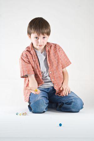 Un garçon joue un jeu de billes. Vertical, studio de portrait isolé.  Banque d'images - 2316459