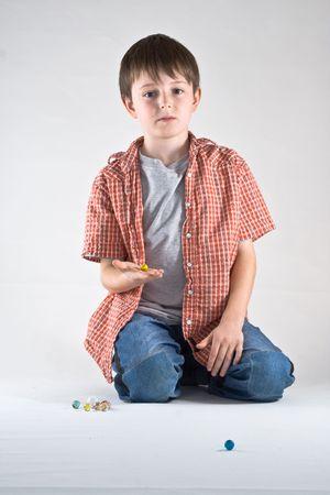 Un garçon joue un jeu de billes. Vertical, studio de portrait isolé.  Banque d'images - 2316457