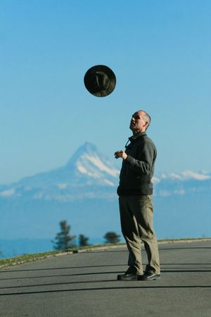 tosses: A man tosses a hat into the air, in front of a chain of mountains.