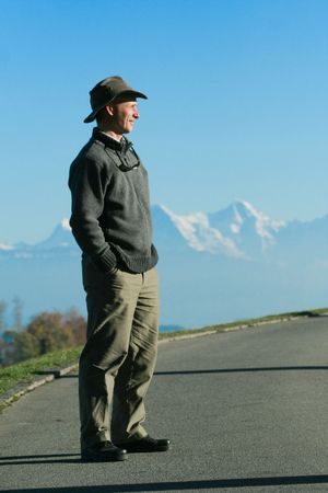 A man smiles as stands, hands in his pockets, surveying the horizon, in front of a chain of mountains in the Fall.